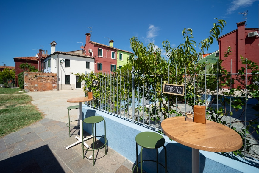 Alfresco outdoor bar tables on the Burano island in Venice Italy Inexhibit