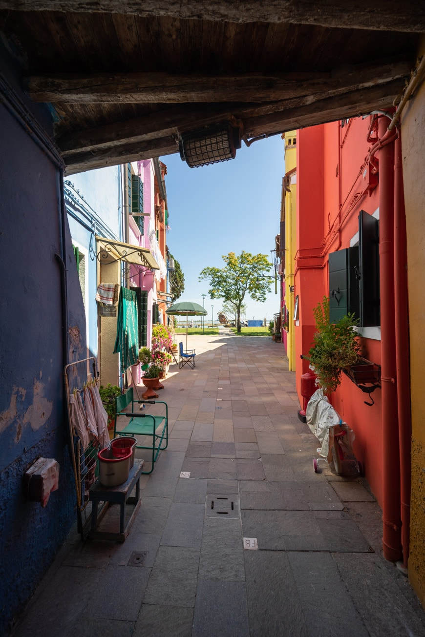 Burano island Venice colored passageway with the Venetian Lagoon in background 2 Inexhibit
